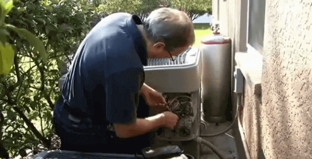 heat pump repairs - technician working on heat pump