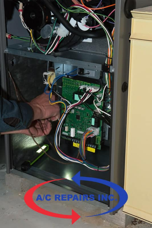 gas furnace repair - service technician working on gas furnace